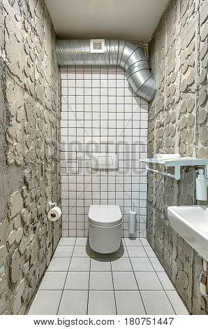 Restroom in a cafe in a loft style with tiled white walls and concrete walls. There is a white toilet, sink, shelf with towels, mirror, paper holder, yellow door. Horizontal.
