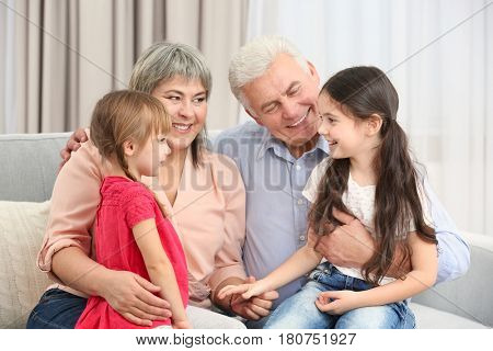 Grand parents and girls on sofa in the room