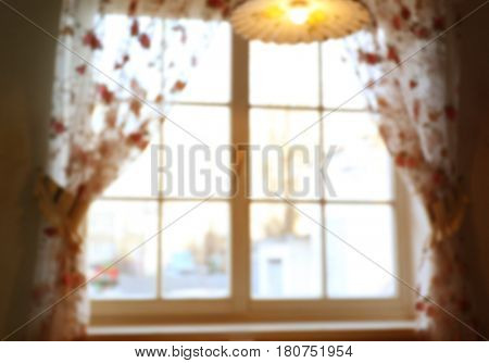 Blurred view of large wooden window with beautiful curtains in sunny day
