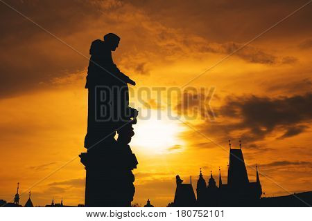 Silhouettes of roofs and statues at sunset in Prague. Statues on Charles Bridge Prague Czech Republic