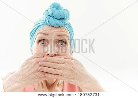 Portrait of old woman is surprised by her wrinkles. She is covering her mouth by hands. Isolated and copy space in right side