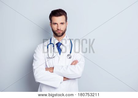 Portrait Of Serious Handsome Male Doctor With Crossed Hands On Gray Background