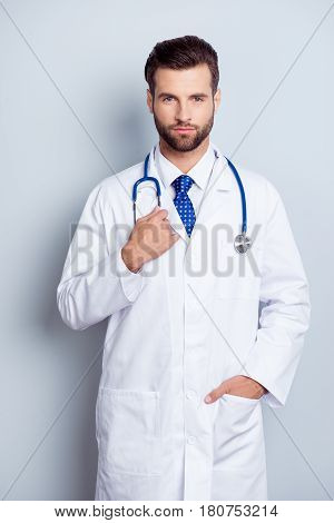 Portrait Of Serious Handsome  Young Male Doctor Holding Hand In Pocket Standing On Gray Background