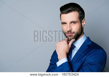 Portrait Of Serious Fashionable Handsome Man In Blue Suit And Tie  Touching Chin And Think