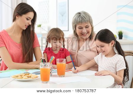 Little girls with grandmother and mother at kitchen table