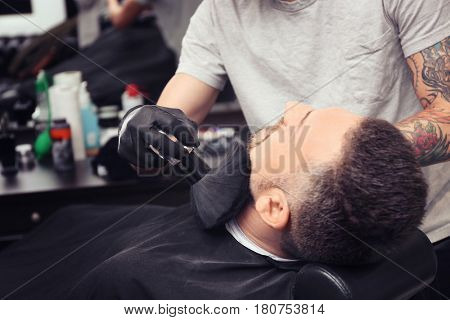 Hairdresser cleaning face of client with brush in barbershop