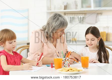 Little girls with grandmother drawing at kitchen table