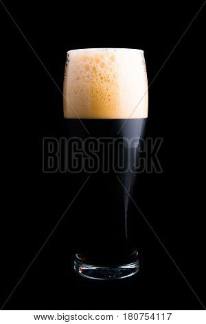 Dark beer in beer glass isolated on black background