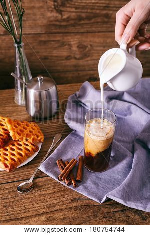 Women's hand, with creamer pouring milk in glass with coffee. Cinnamon sticks, homemade cookies and bunch of wildflowers on a wooden background. Breakfast concept.