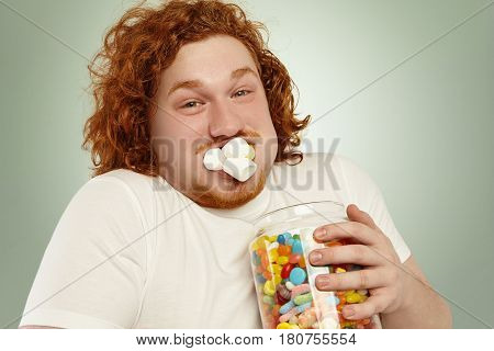 Gluttony, Obesity, Junk Food And Unhealthy Lifestyle. Funny Redhead Obese Young Man Holding Big Jar