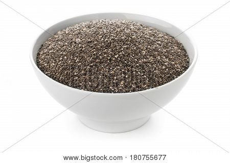Raw unprocessed dried black chia seeds in white bowl on white background