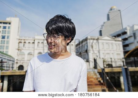 Young adult asian guy smiling photoshoot outdoors