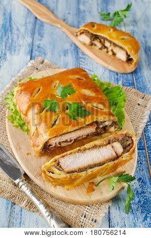 Turkey fillet with mushrooms baked in puff pastry. Meat in a cut on a wooden cutting board