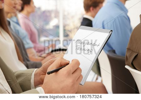 Man holding notebook with text MANAGEMENT TRAINING at business presentation