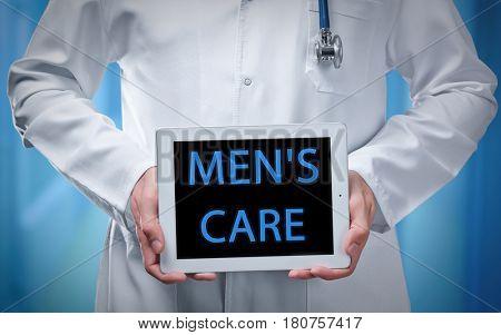 Doctor holding tablet with text MEN'S CARE on screen, closeup. Health care concept