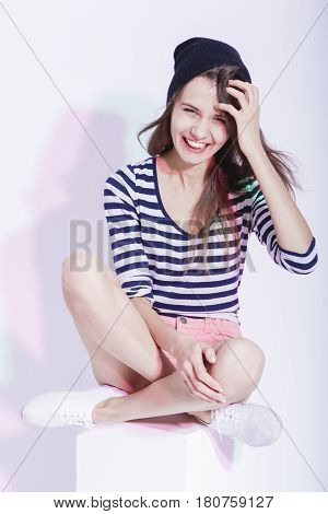 Youth Lifestyle Concepts and Ideas. Portrait of Happy Smiing Caucasian Brunette in Hat and Striped Shirt Posing in Studio Against White. Vertical Image