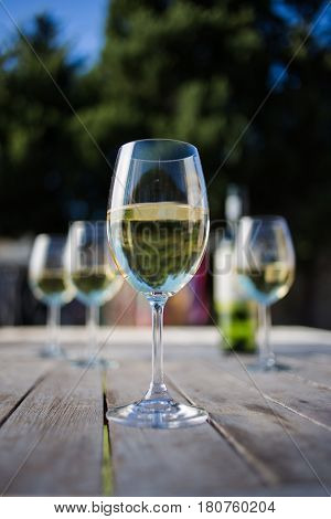 Close Up Image Of White  Wine Being Poured Into A Glass On A Wooden Table Outside With Natural Light