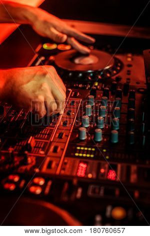 Dj Playing Music In Night Club Party. Turntable Equipment In Dark Red