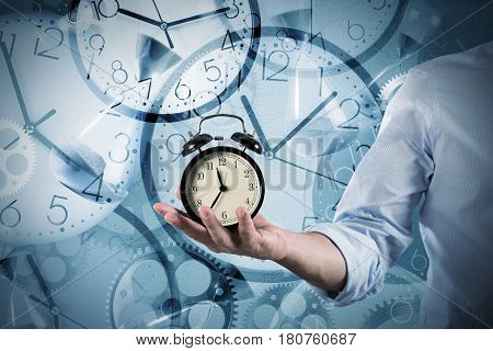 Businessman holds an alarm clock in his hand on clocks that mark many times