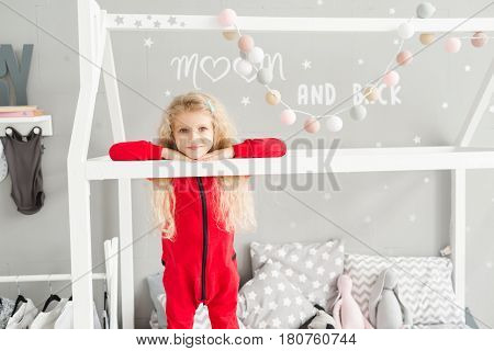Little girl with white curly hair in red pajamas laughing at children's room