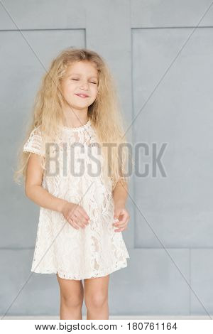 Little cute girl with curly blonde hair in a lace dress on the background of blue wall