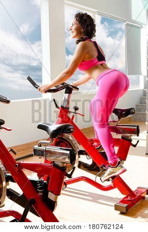 Fitness woman exercising on a spinning cycle in gym. Caucasian young female athlete doing fitness training on a stationary bike.