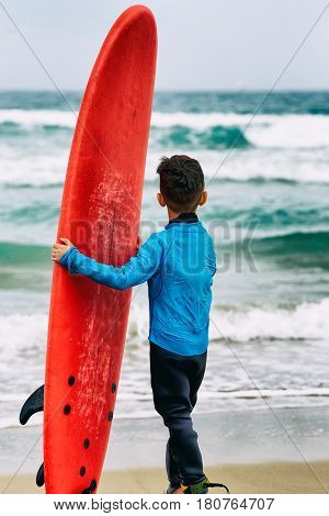 Young pretty surfer with wet suit boy holding red surfboard on the beach from behind.