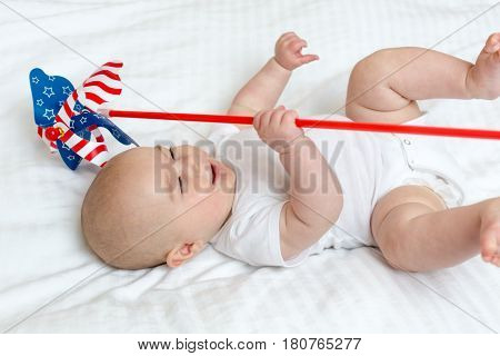 Happy Newborn Baby Girl Playing With A Pinwheel