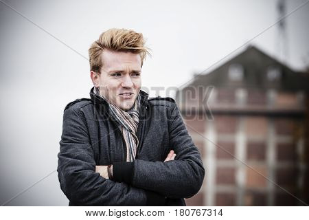 Young handsome freezing man fashion model casual style on street urban industrial background. Cold foggy day