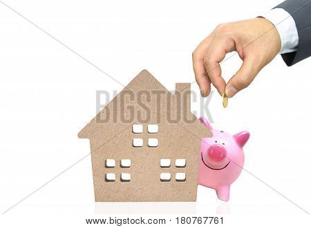 A pink piggy bank with a wooden house / Saving money for buying a house concept