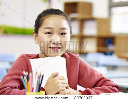 portrait of an asian elementary schoolgirl looking at camera smiling.