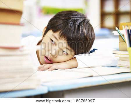 asian elementary schoolboy tire and resting head on desk.