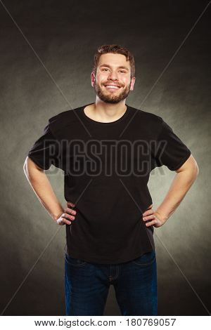 Portrait of happy handsome fashionable man in black blank shirt with empty copy space. Young guy in studio on black. Casual fashion advertisement.