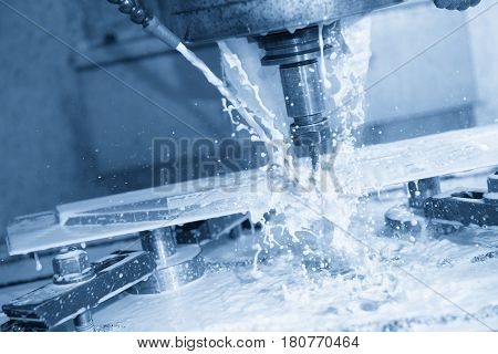 The CNC milling machine cutting the part using the coolant with the light blue scene