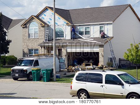 JOLIET, ILLINOIS / UNITED STATES - SEPTEMBER 7, 2016: Carpenters replace the siding on a home in the Wesmere Estates neighborhood of the Wesmere Country Club in Joliet.