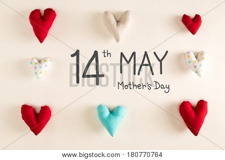 Mother's Day message with blue heart cushions on a white paper background