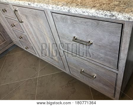 Kitchen cabinet. Modern inset kitchen cabinet with granite countertop. Handles on kitchen cabinet. Contemporary kitchen cabinet design. Gray wooden kitchen cabinet on tile floor.
