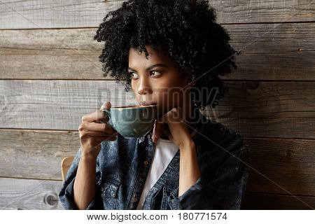 Attractive Afro American Hipster Girl Dressed Stylishly Drinking Coffee Or Tea Thoughtfully Out Of B
