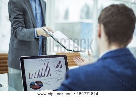 closeup of the accountant, passes into the hands of the Manager Finance financial report for the workplace in the office