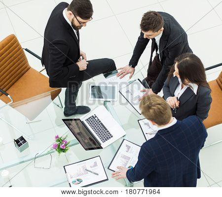 top view of successful business team discussing marketing graphics before the meeting in a modern office .
