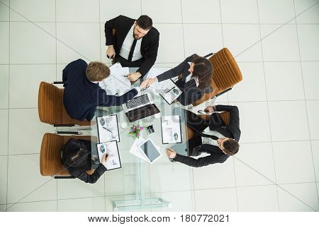 top view of business partners shaking hands after a discussion of the new fiscal Treaty.the photo is a blank space for your text