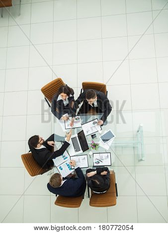 top view of business team and reliable business partners stretch forward hands to each other for a handshake after the debate on the new Finance contract at a Desk in the spacious office.the photo has a empty space for your text
