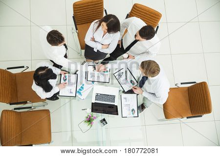 top view :successful business team shaking hands with new business partners after the conclusion of the financial contract in the conference room.the photo has a empty space for your text