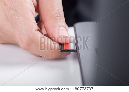 Hand Inserting Sd Card Into Laptop