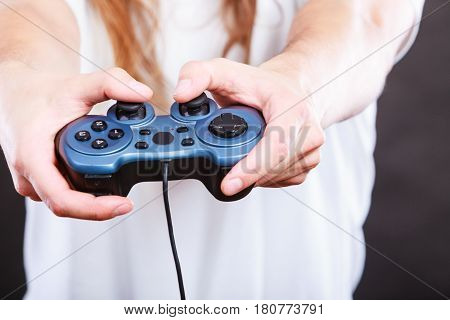 Playing games concept. Part body man with joystick play game on console playstation. Male hands holding grey pad.