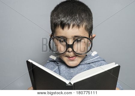 Curiosity Boy with giant glasses reading a book with funny and varied gestures
