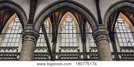 AMSTERDAM (NETHERLANDS) - CIRCA JANUARY 2017: Tall graceful Gothic renaissance windows behind stone arches in a historic Dutch church in Amsterdam Netherlands in an architectural background view