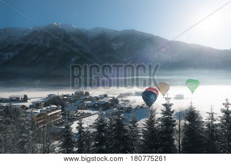 ACHENKIRCH (AUSTRIA) - CIRCA MARCH 2017: Hot air balloons flying above an alpine resort in a snowy valley on a cold misty winter day in early morning