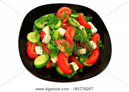Mediterranean style salad from tomato wedges sliced seedless cucumber Feta cheese seasoned with green onion parsley and dill served on a black porcelain dish over white background