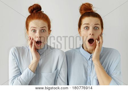 Studio Shot Of Two Scared Caucasian Female Students With Same Hair Buns, Wearing Similar Formal Shir